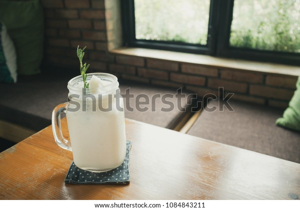 fresh coconut water frappe with rosemary leaf on restaurant table