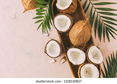 Fresh coconuts with coconut halves on a pink background, top view. Copy space.