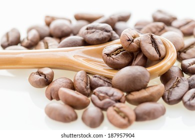 Fresh coffee beans with brown coffee spoon on white background