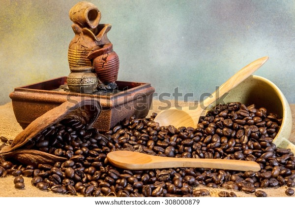 Fresh coffee beans on sackcloth with a wooden spoon and coffee mugs.