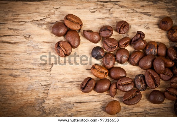 Fresh coffee beans on wood and linen bag, ready to brew delicious coffee