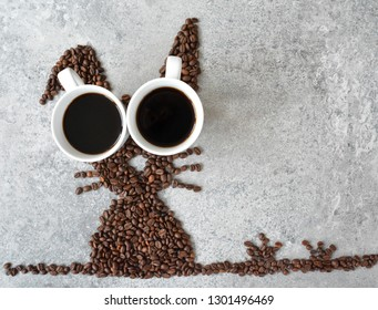 With fresh coffee beans and two cups of freshly brewed black coffee, a hare is shaped on a bright marble surface - concept with coffee beans as a gift for Easter - with room for text or other elements