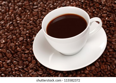 Fresh coffee in a cup surrounded by coffee beans