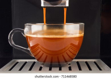 Fresh coffee prepared in the machine. Espresso glass cup.