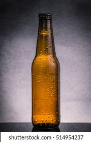 fresh cold beer ale bottle with drops and stopper on dark black background