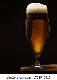 Fresh cold beer in a glass on wooden table on black background.