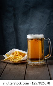 Fresh cold beer with spices french fries on wooden table in front of painted backdrop