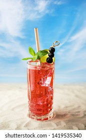 Fresh cold cocktail with ice and fruits by beach