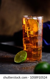 Fresh cold ice tea with lemon, lime on rustic background.