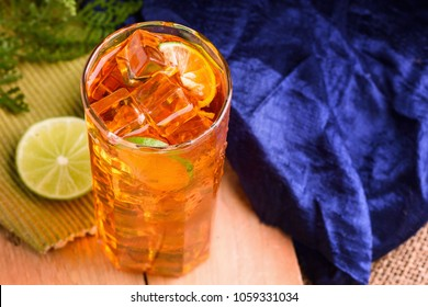 Fresh cold ice tea with lemon, lime and green leaf/ blue fabric/napkin on  wooden table