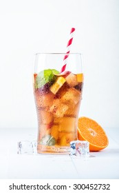 Fresh cold ice tea with orange, mint and ice cubes in the glass on white background