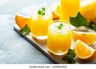 Fresh cold orange juice with green mint and ice, selective focus