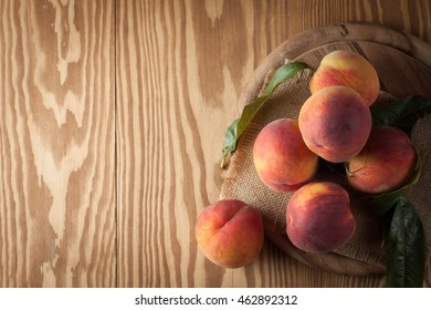 Fresh, cold peach tea with mint, ice cubes and peaches fruits on wooden background.