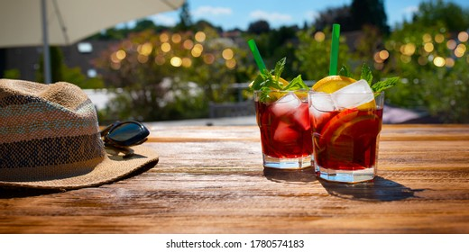 Fresh cold sangria cocktail on a summer evening. Still life with short depth of field on a terrace with fairy lights in background. Vacation and leisure lifestyle.