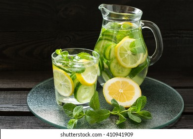 Fresh cold water with lemon, cucumber, ginger, mint and ice in a pitcher and glass on a glass tray