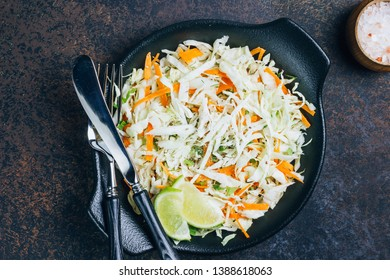 Fresh coleslaw salad in black plate on dark background. Fresh cabbage and carrot salad. Top view