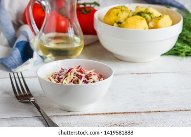 fresh coleslaw salad boiled potato with dill  glass bottle of oil fork on wooden table
