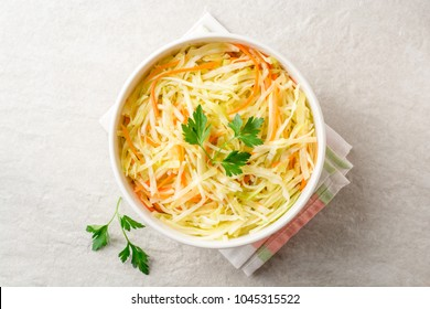 Fresh coleslaw salad in bowl on gray stone background. Top view. Copy space.