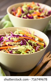 Fresh coleslaw, a salad made of shredded red and white cabbage and carrots, served in white bowls, photographed with natural light (Selective Focus, Focus in the middle of the salad)