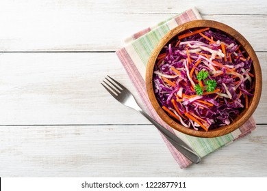 Fresh coleslaw salad with red and white cabbage and carrots in bowl on white wooden background. Top view. Copy space.