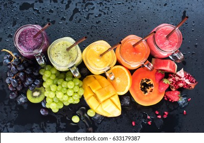 Fresh Color Juices Smoothie Violet Green Yellow Orange Red from Tropical Fruits Kiwi Water Melon Strawberry Apple Orange Banana Pine Apple Bottles multi-colour rainbow Dark Background