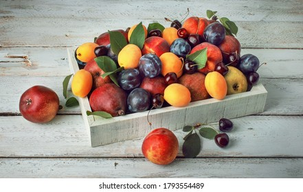 Fresh colorful berries and fruits in a box on a wooden table, harvesting