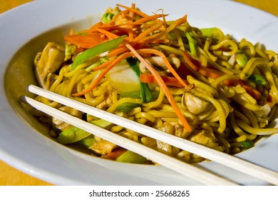 Fresh colorful lo mein in a white bowl with chopsticks