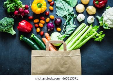 Frische, bunte organische Gemüsesorten aus Papier-Öko-Einkaufstasche - von oben gefangen (Draufsicht, flache Lage). Schwarze Tafel (Tafel) als Hintergrund.