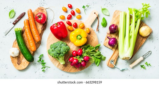 Fresh colorful organic vegetables on wooden chopping (cutting) boards captured from above (top view, flat lay). Grey stone worktop as background. Kitchen - preparing food.