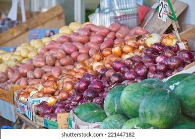 Fresh colorful produce in a Jerusalem fruit and vegetable market: assorted onion and potatoes, and watermelon