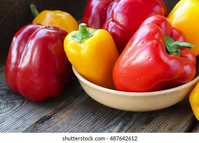 Fresh colorful red and yellow paprika peppers on a wooden background, selective focus