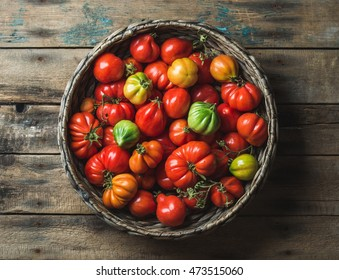 Fresh colorful ripe Fall heirloom tomatoes in basket over wooden background, top view, horizontal composition