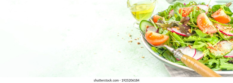 Fresh colorful spring salad – with tomatoes, avocado, walnuts, cucumber, spring radish, on light green background copy space. Spring diet healthy food concept