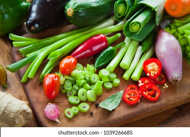 Fresh colorful Vegetable ingredient board - aubergine, courgette, leek, carrot, onion, spring onions, chive, shallot, tomato, celery,  bell pepper, chili pepper, ginger, garlic, bay leaves, peppercorn