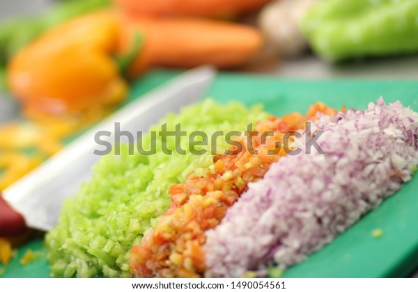 Fresh colorful vegetables cut into small pieces ready for cooking or to prepare a delicious vegan salad.