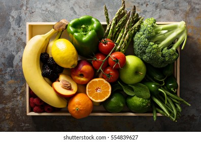 Fresh and colorful vegetables and fruits in a wooden crate