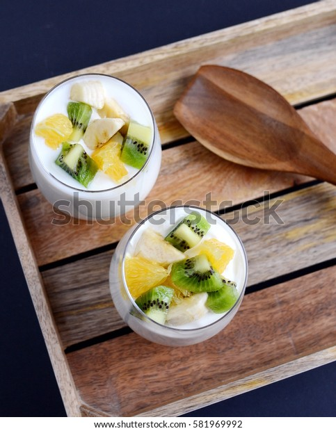 Fresh colorful vitamin breakfast, yogurt with pieces of fruits, kiwi, banana, orange, in glass cups
