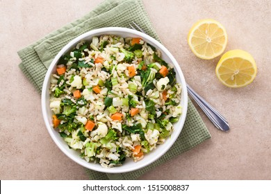 Fresh cooked brown rice with steamed vegetables (broccoli, cauliflower, swiss chard, carrot, celery) in bowl, photographed overhead with lemon on the side