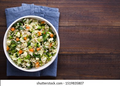 Fresh cooked brown rice with steamed vegetables (broccoli, cauliflower, swiss chard, carrot, celery) in bowl, photographed overhead with copy space on the right side