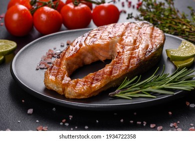 Fresh cooked delicious salmon steak with spices and herbs baked on a grill. Healthy seafood food