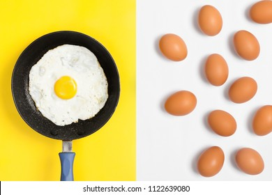 Fresh cooked egg in a pan with uncooked eggs randomly placed over white background. Lay flat image.