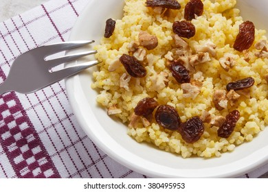 Fresh cooked millet groats with raisins and walnuts on white plate, concept of healthy food, nutrition and nutritious breakfast