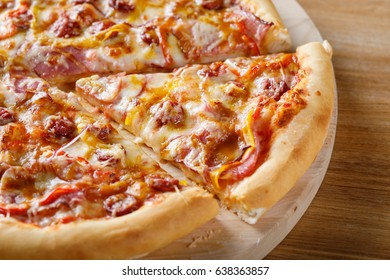 Fresh cooked pizza on wooden board. Close-up view of piece of pizza