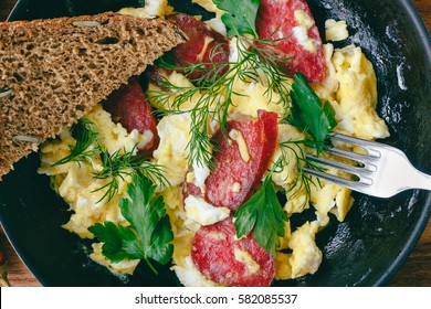 Fresh cooked scrambled eggs in pan with sausage, herbs, fork and bread, close-up, top view