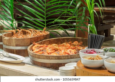 Fresh cooked tiger prawns and crabs on ice in wooden bucket served at seafood market buffet.
