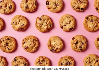 Fresh cookies with cranberries and white chocolate pattern on pink background