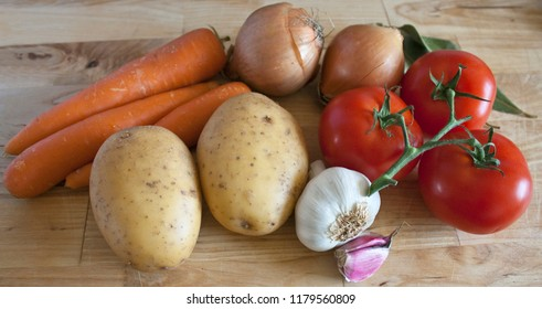 Fresh cooking ingredients: some tomatoes, onions, carrots, potatoes, garlic and laurel on a wooden chopping board.