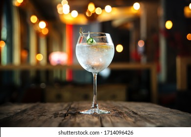 Fresh cool cocktail gin tonic on the wooden table in the bar, horizontal