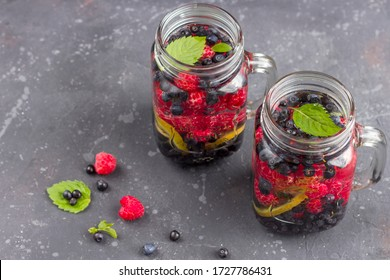 Fresh cool detox drink with raspberries, blueberries and kiwi in mason jar mug. Lemonade in a glass with a mint. The concept of proper nutrition and healthy eating. Fitness diet. Copy space for text