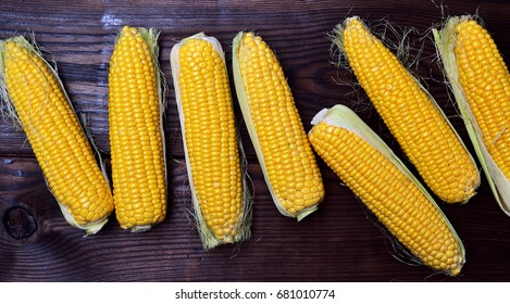 Fresh corn cobs on a brown wooden background, top view
